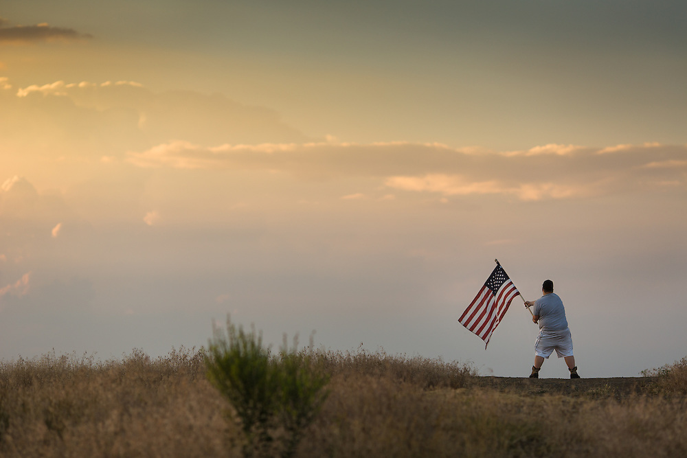 "Andy Binford waves an American flag at sunset Monday in Coeur d'Alene as he prepares to celebrate Independence Day. ""I like making art and I'm out here to make the patriots, my parents and my family proud,"" Binford said as the sun slipped below the horizon."