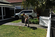 A golfer plays from the front yard of a house on World Urban Golf Day in Newcastle, Australia. Played with soft balls and without keeping score, Urban Golf is an attempt to take the game of golf away from the manicured lawns and into the urban environment.environment.