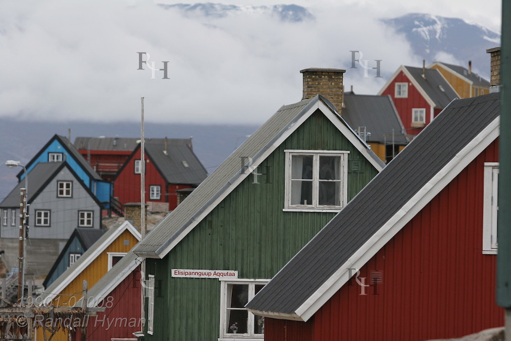 Colorful buildings overlook fjord on a late August day in the island town of Uummannaq, Greenland.