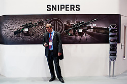 DSEI arms fair in London.<br /> A businessman stands by snipers on display at the SIG stand during the 2013 edition of DSEI at Excel London, United Kingdom. Tuesday, 10th September 2013. Picture by Piero Cruciatti / i-Images