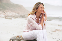 Woman sitting on boulder on beach smiling
