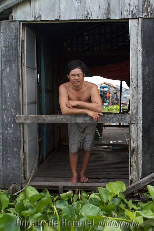 A fisherman in the Mekong Delta takes a break in his fish farm. Fish farms in the Mekong Delta in Vietnam  are often floating houses with big cages under the house holding the fish. They make their own fish feed from agricultural waste and small fish, the only fish still being caught in the river. .Fish levels have gone down drastically since several years. Dam construction in the upper stretches of the Mekong River in China are blamed for this.