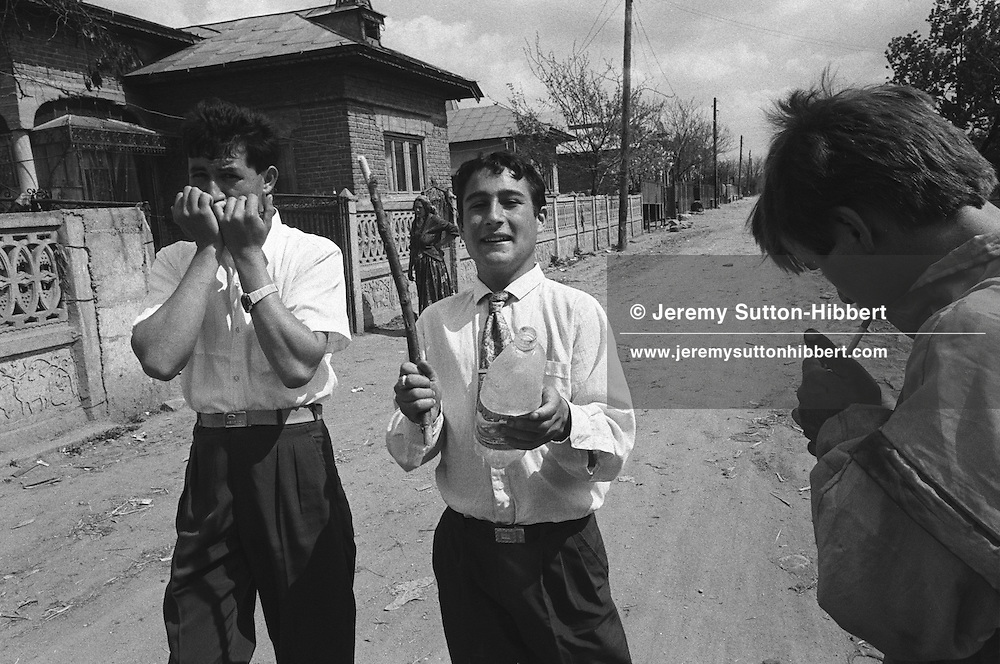 Two Kalderash gypsy youths play music on a harmonica and a plastic bottle as part of their celebrations of Romanian Orthodox Easter, the most important date in their calendar, in the Kalderash Roma camp of Sintesti, near Bucharest.