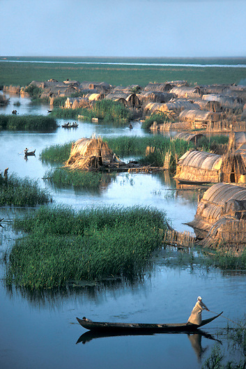 Iraqi Marsh Arab paddles his canoe through reed hut village in the marshlands of Southern Iraq where the Tigris and Euphrates Rivers meet