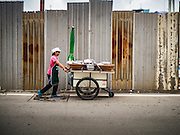 21 SEPTEMBER 2016 - BANGKOK, THAILAND: A woman pushes her vending cart past the fence the encloses the construction site at the old Bang Chak Market. The market closed permanently on January 4, 2016. The Bang Chak Market served the community around Sois 91-97 on Sukhumvit Road in the Bangkok suburbs. Bangkok city authorities put up notices in late November 2015 that the market would be closed by January 1, 2016 and redevelopment would start shortly after that. Market vendors said condominiums are being built on the land.      PHOTO BY JACK KURTZ