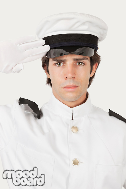 Portrait of young navy officer saluting against gray background