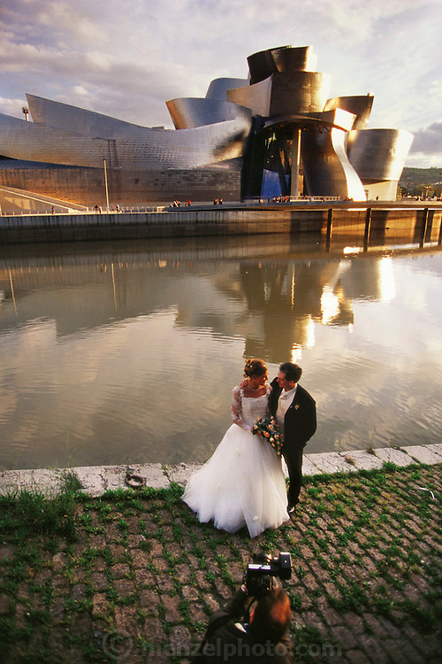 Newly married couple being photographed across the river from the Guggenheim Art Museum, Bilbao, Spain. Frank Gehry, architect.