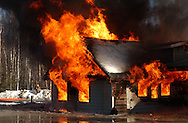 A house is fully engulfed in flame at the conclusion of a training fire in Alaska.
