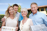Young couple and older couple standing outside holding presents