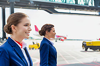 Photo of confident flight attendants walking against airplane in airport