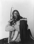 Native American man, three-quarter length portrait, seated, facing right; arms folded, holding bow, arrow, and tomahawk; dressed in bone breast plate. Photograph by Heyn and Matzen 1900