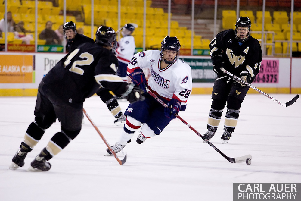 October 13, 2007 - Anchorage, Alaska: Scott Kobialko (28) of the Robert Morris Colonials pushes the puck into the Warrior zone as Ryan Adams (42) of the Wayne State Warriors tries to stop him as the Colonials take a 4-1 victory over the Wayne State Warriors at the Nye Frontier Classic at the Sullivan Arena.