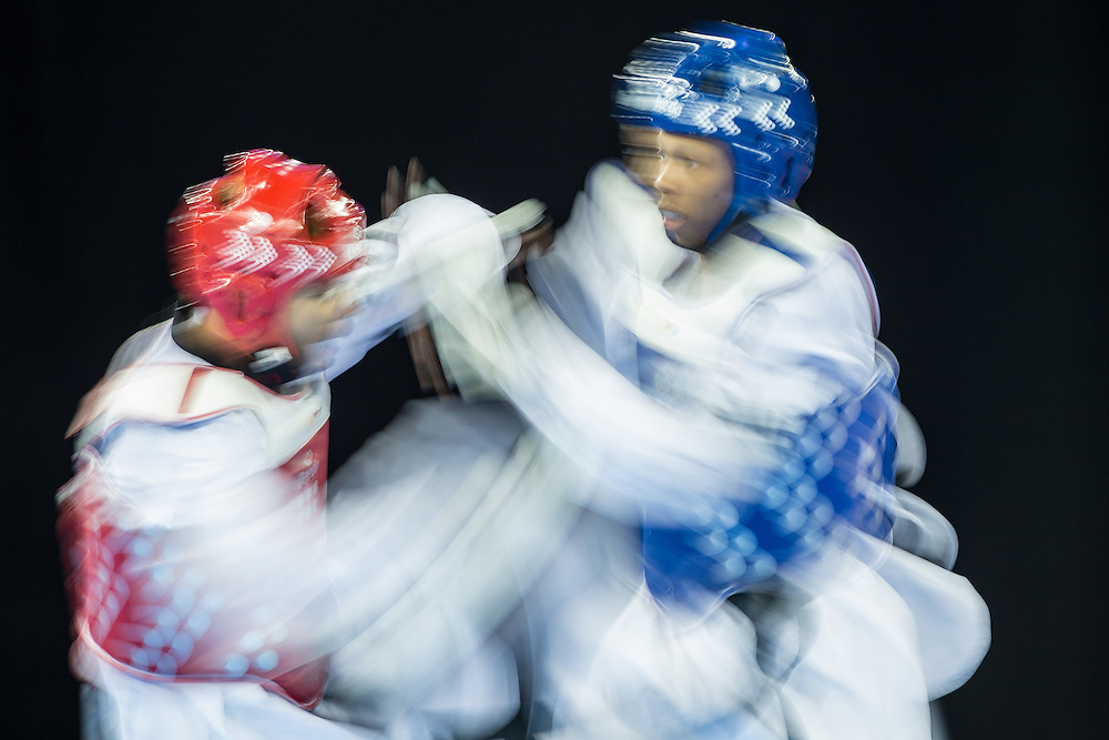 Fermin Quesada of Cuba takes on Edgar Contreras of Venezuela during their 1/8 round contest in the -68kg weight class of Taekwondo at the 2015 Pan American Games in Toronto, Canada, July 20,  2015.  AFP PHOTO/GEOFF ROBINS