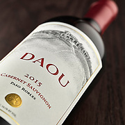 Bottle of Daou Cabernet Sovignon lying on its side on a piece of mahogony wood.