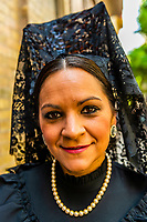 Spanish women wearing mantillas (head scarves), Holy Week (Semana Santa), Seville, Andalusia, Spain.
