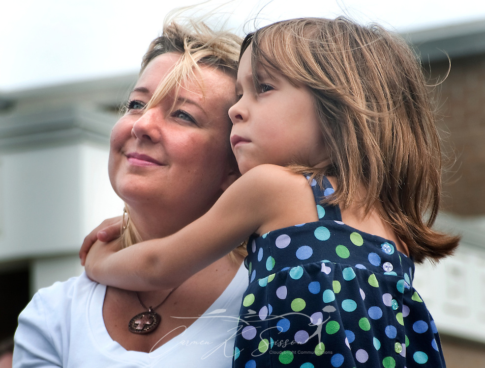 "Tonya Schevers holds her daughter, Marlee Schevers, 7, during a ceremony commemorating the fifth anniversary of Hurricane Katrina Aug. 29, 2010 in Gulfport, Miss. ""We have a long way to go, but we've come a long way in a short time,"" Schevers said. Approximately 231 people died in Mississippi during Katrina, and some infrastructure is still in ruins. (Photo by Carmen K. Sisson/Cloudybright)"