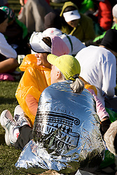 runners in plastic and foil blankets wait in runner's village prior to race