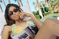 Woman in bikini sitting on deckchair and using mobile phone