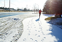 Erickson makes his way along a snow-covered pathway beside Ramsey Road during one of his shorter runs Wednesday.