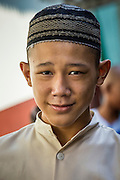 "11 JANUARY 2013 - BANGKOK, THAILAND:   A boy from the local Muslim school in the Ban Krua neighborhood in Bangkok. The Ban Krua neighborhood of Bangkok is the oldest Muslim community in Bangkok. Ban Krua was originally settled by Cham Muslims from Cambodia and Vietnam who fought on the side of the Thai King Rama I. They were given a royal grant of land east of what was then the Thai capitol at the end of the 18th century in return for their military service. The Cham Muslims were originally weavers and what is known as ""Thai Silk"" was developed by the people in Ban Krua. Several families in the neighborhood still weave in their homes.                 PHOTO BY JACK KURTZ"