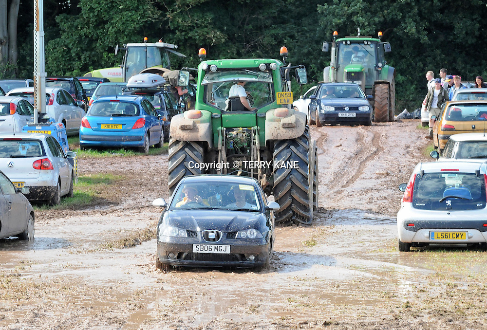 DARESBURY, UK:.Cars get towed out by tractors from the car park mud..Creamfields festival closed early by extreme weather  on Sunday, 26th August 2012..PHOTO BY TERRY KANE.+44 (0)7974 921 220.www.eyewitnessimages.co.uk