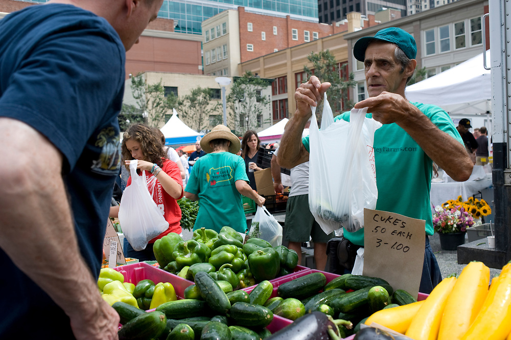 Dick Moran, right, of Harvest Valley Farms, prepares an order at the Market Square Farmers Market in downtown Pittsburgh. The market is held every Thursday until November.