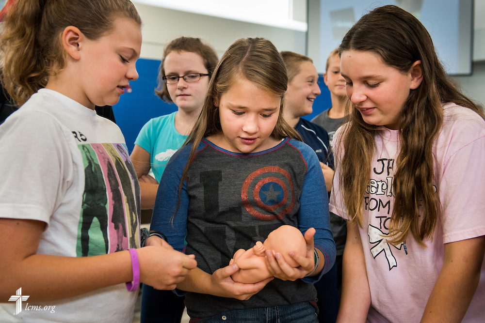 Students examine a fetal development model following an Owen's Mission presentation at Trinity Lutheran School on Monday, August 31, 2015, in Bloomington, Ill. LCMS Communications/Erik M. Lunsford