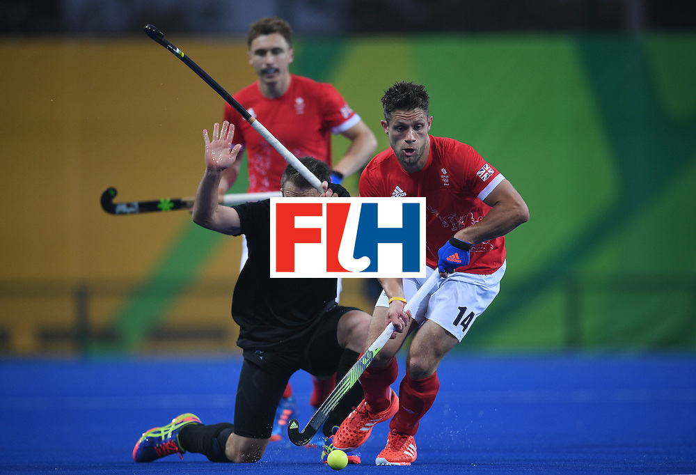 New Zealand's Shea McAleese (C) gestures as Britain's Mark Gleghorne controls the ball during the men's field hockey Britain vs New Zealand match of the Rio 2016 Olympics Games at the Olympic Hockey Centre in Rio de Janeiro on August, 7 2016. / AFP / MANAN VATSYAYANA        (Photo credit should read MANAN VATSYAYANA/AFP/Getty Images)