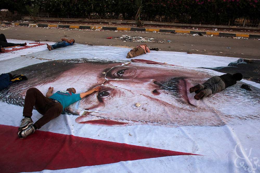 Supporters of deposed Egyptian President Mohamed Morsi sleep on a giant poster of him Monday morning August 12, 2013 on the edges of the thousands strong sit-in at the Rabaah al-Adawiya square in the Nasr City District of Cairo Egypt. They have remained camped there for more than a month now vowing to stay until the president is returned to power, yet authorities have threatened to close the camp by force within days.