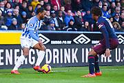 Jason Puncheon of Huddersfield Town (42) takes on Alex Iwobi of Arsenal (17) during the Premier League match between Huddersfield Town and Arsenal at the John Smiths Stadium, Huddersfield, England on 9 February 2019.