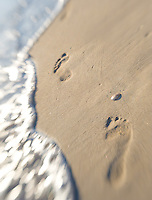 Footprints lead into frame along water's edge on a white sand beach. Travel photography by Djuna Ivereigh.