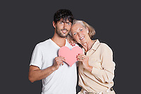 Senior woman and young man holding red paper heart against black background