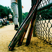 Baseball bats leaning against a fence on a baseball field, USA, 1990's