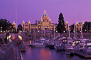 Parliament Building at dusk and boats in Inner Harbour; Victoria, Vancouver Island, British Columbia, Canada.
