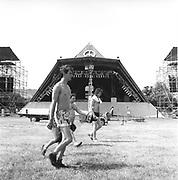 People walking past the Pyramid Stage, Glastonbury, Somerset, 1989