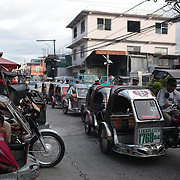 A Street Scene in Laoag City, Ilocos Norte, the Philippines on September 26, 2008 as motorized tricycles are used as taxi's. Photo Tim Clayton