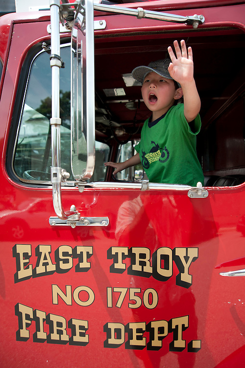 Holden Miller, 4, pretends to drive a fire truck before the start of a July Fourth holiday parade in rural East Troy, Wis., on July 3, 2011.