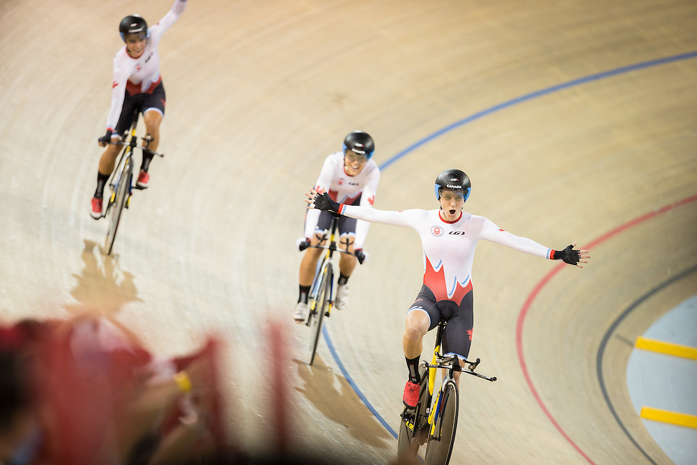 Laura Brown (R) of Canada celebrates her team's gold medal win in the women's cycling team pursuit with teammates Jasmin Glaesser (L) and Kirsti Lay at  at the 2015 Pan American Games in Toronto, Canada, July 17,  2015.  AFP PHOTO/GEOFF ROBINS