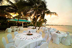 Tables set up for an event at Victoria House on a beach at sunset in Ambergris Caye, Belize.