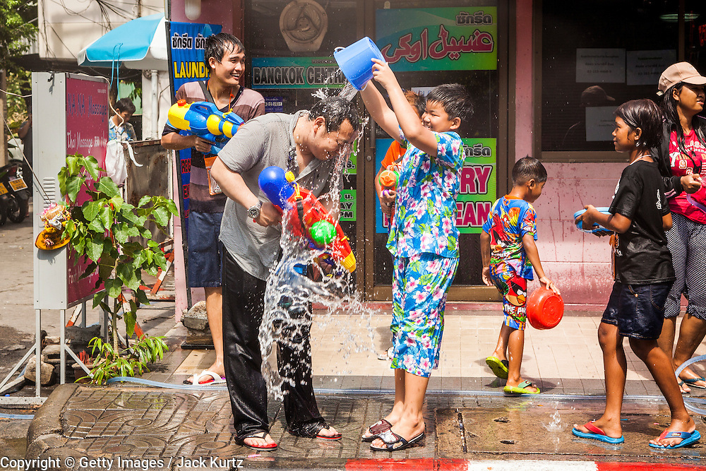 14 APRIL 2013 - BANGKOK, THAILAND:  A boy uses a bucket to throw water on a tourist on Soi Nana on April 14, 2013 in Bangkok, Thailand. The Songkran festival is celebrated in Thailand as the traditional New Year's Day from 13 to 15 April. The throwing of water originated as a way to pay respect to people and is meant as a symbol of washing all of the bad away. PHOTO BY JACK KURTZ
