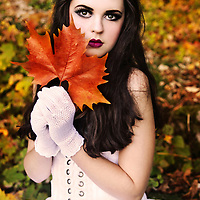A girl in a white dress with long black hair and dramatic make-up, holding a red leaf and looking at camera.