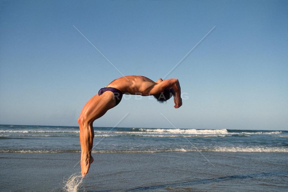 Sexy man doing a backflip at the beach in Santa Monica, CA