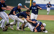 Bon Homme/Scotland's Bryce Scieszinski (12) is the first to jump on the pile of Bon Homme/Scotland's Trent Herrboldt (5) after Herrboldt records the final out to win the Class B state championship 7-5 over West Central on Tuesday at the Sioux Falls Stadium. (Matt Gade / Republic)
