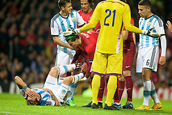 MANCHESTER, ENGLAND - Tuesday, November 18, 2014: Portugal's captain Cristiano Ronaldo checks on the well-being of Argentina's Lucas Biglia after kicking him in the stomach during the International Friendly match at Old Trafford. (Pic by David Rawcliffe/Propaganda)