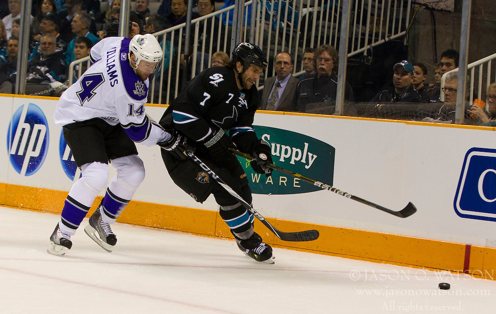 April 14, 2011; San Jose, CA, USA; San Jose Sharks defenseman Niclas Wallin (7) fights for the puck against Los Angeles Kings right wing Justin Williams (14) during the first period at HP Pavilion. Mandatory Credit: Jason O. Watson / US PRESSWIRE