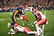 Denver Broncos rookie running back Royce Freeman (28) runs through a trio of Kansas City Chiefs defenders as he for a 14 yard touchdown that ties the second quarter score at 10-10 during the NFL week 4 regular season football game against the Kansas City Chiefs on Monday, Oct. 1, 2018 in Denver. The Chiefs won the game 27-23. (©Paul Anthony Spinelli)