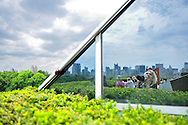 Manhattan skyline view, partly reflected in mirrored wall of roof, from rooftop of Metropolitan Museum of Art roof cafe, on 5th Avenue, Manhattan, New York City, NY, USA, July 2011