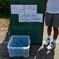 © Licensed to London News Pictures. 06/07/2018. LONDON, UK. Bottled water is for sale to spectators making their way to the Wimbledon Tennis Championships.  Temperatures forecast to approach 30C mean that the majority have taken precautions to protect themselves from the sun by wearing sunglasses and sunhats.  Photo credit: Stephen Chung/LNP