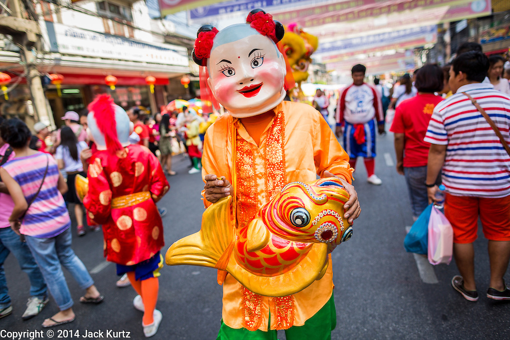 31 JANUARY 2014 - BANGKOK, THAILAND:   A member of a Lion dancer troupe walks down a street during Lunar New Year festivities, also know as Tet and Chinese New Year, in Bangkok. This year is the Year of the Horse. The Lion Dance scares away evil spirits and brings prosperity and luck. Ethnic Chinese make up about 14% of Thailand and Chinese holidays are widely celebrated in Thailand.     PHOTO BY JACK KURTZ