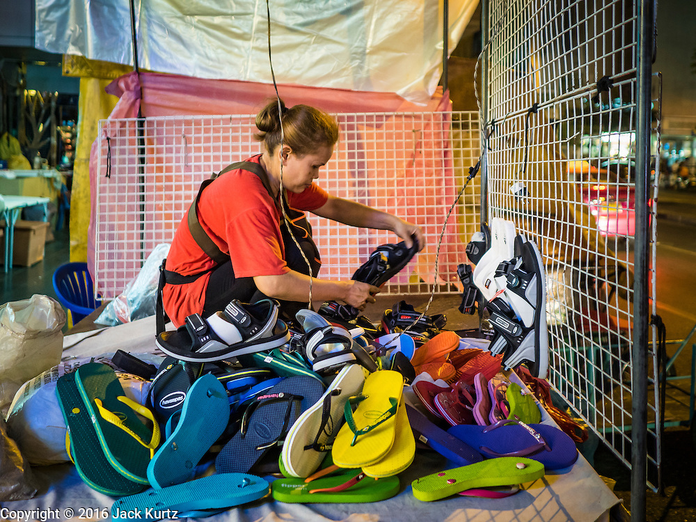 26 MAY 2016 - BANGKOK, THAILAND: A woman who sells shoes and flip-flops in the Silom Road night market sets up her stand before the market opened. The night market on Silom Road, close to Bangkok's famous Patpong tourist area, is being closed by the Bangkok municipal government. Vendors have been told they have to leave the sidewalk on Silom Road by the end of May, 2016. The market is the latest street market being shut down by city officials as a part of the government's plan to clean up Bangkok. The Silom Road night market sells mostly tourist oriented clothes, inexpensive Thai art, and bootleg movies on DVD.       PHOTO BY JACK KURTZ
